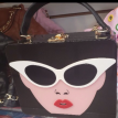 Lady's face purse with cat eye glasses.